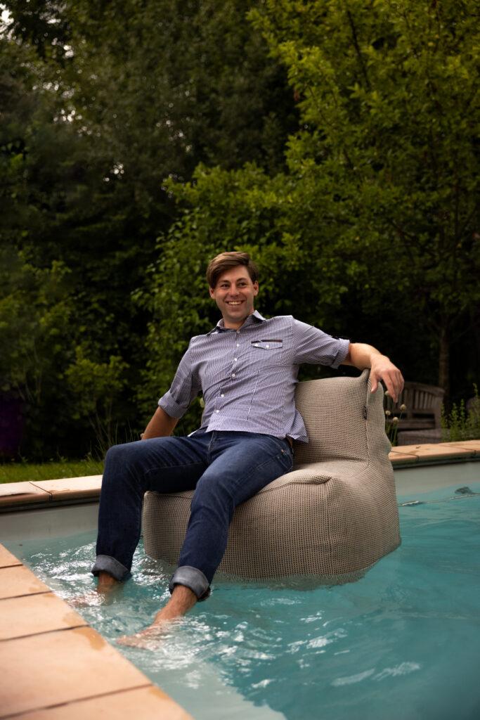 Ein Herr, der auf einem Sitzsack im Pool sitzt.