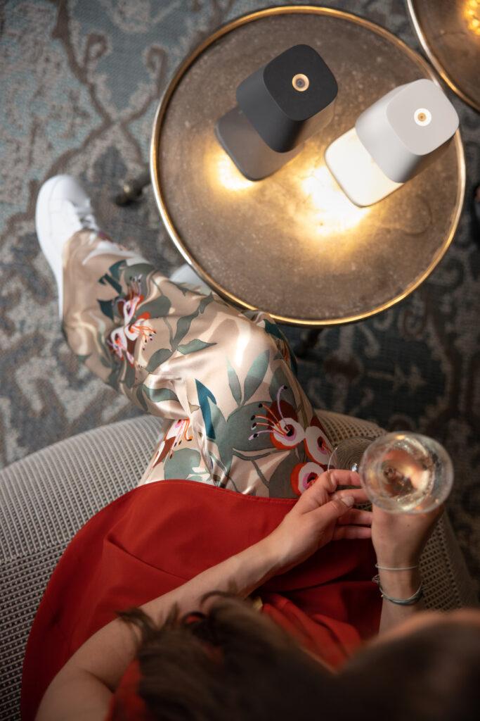 Das Outfit einer Dame ist zum Teil zu sehen, sowie ein Beistelltisch mit zwei LED-Lampen.