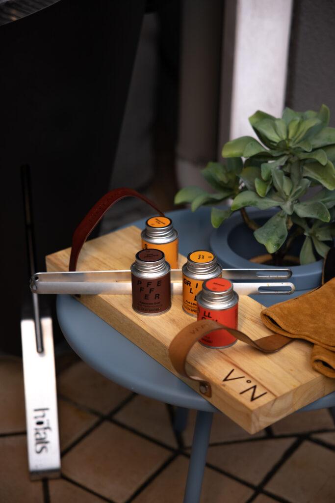 Verschiedene Grillgewürze und eine Grillzange auf einem Holzbrett.